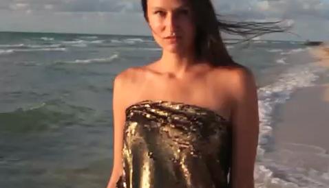 La modella posa sulla spiaggia. Alle sue spalle sbarcano i clandestini