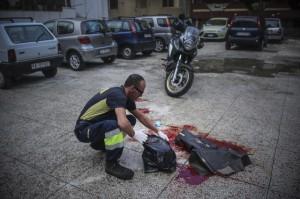 """Un operatore ecologico napoletano rimuove le tracce di sangue dell'agguato in cui Domenico Aporta, 24 anni, con precedenti penali e ritenuto vicino al clan di camorra """"Vinella Grassi"""", e' stato ucciso con almeno un colpo di arma da fuoco alla testa nella notte a San Pietro a Patierno, alla periferia di Napoli, 17 ottobre 2015. Nell'agguato, il fratello Mariano, di 21 anni, incensurato, è rimasto ferito ad un braccio."""
