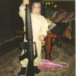 La figlia dell'uomo sottoposto a fermo, fotografata mentre imbraccia un fucile più alto di lei. (Foto Facebook)