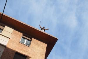 Un occupante posizionato in cima a uno stabile, mentre in strada avvengono scontri tra manifestanti e agenti di polizia a Bologna, dove è in corso lo sgombero di un immobile occupato abusivamente in via Irnerio