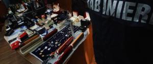 I carabinieri mostrano gli oggetti recuperati nella valigia del narcos