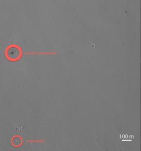 Il cratere nero provocato sulla superficie di Marte dal violento impatto del Lander Schiaparelli, pesante 500 chili, precipitato a 300 chilometri orari. In basso il paracadute, chiaro, atterrato più a sud