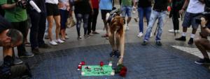 Una ragazza posa dei fiori sulla Rambla di Barcellona dopo l'attentato