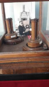 Il telefono di Antonio Meucci e, sullo sfondo, l'inventore davanti alla sua fabbrica di candele a Staten Island